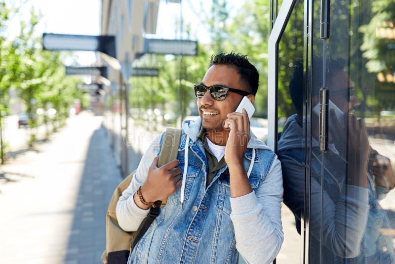 Man med ryggsäcken som kallar på smartphonen i stad arkivfoton