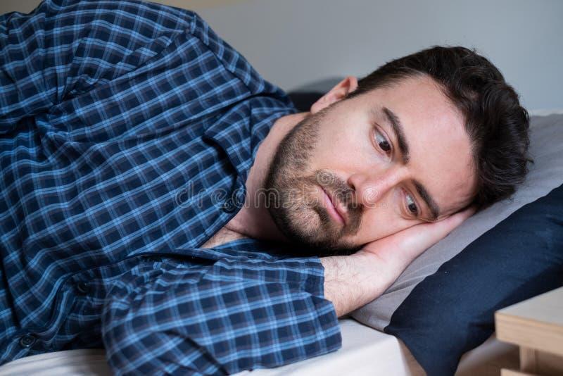 Man med sömnoordning som ligger i sängen royaltyfri foto