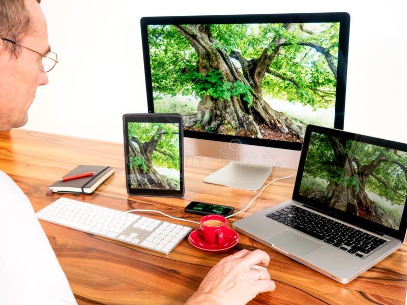 Man med sammankopplade datorer och mobila enheter arkivbilder