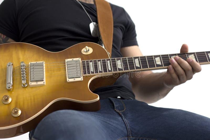 Man med sammanträde för elektrisk gitarr som isoleras över vit royaltyfri bild