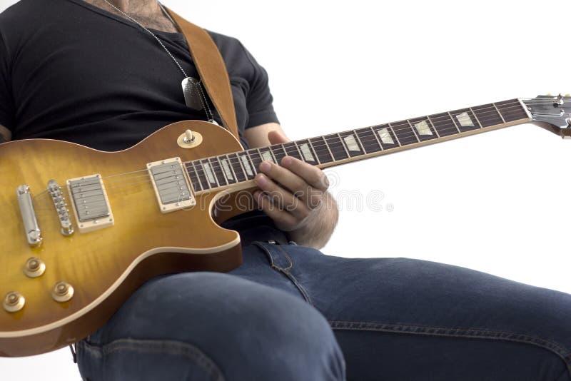 Man med sammanträde för elektrisk gitarr som isoleras över vit royaltyfria bilder