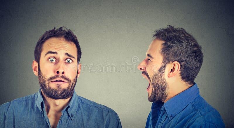 man med schizofreni Ilsken man som skriker på förskräckt själv royaltyfri bild