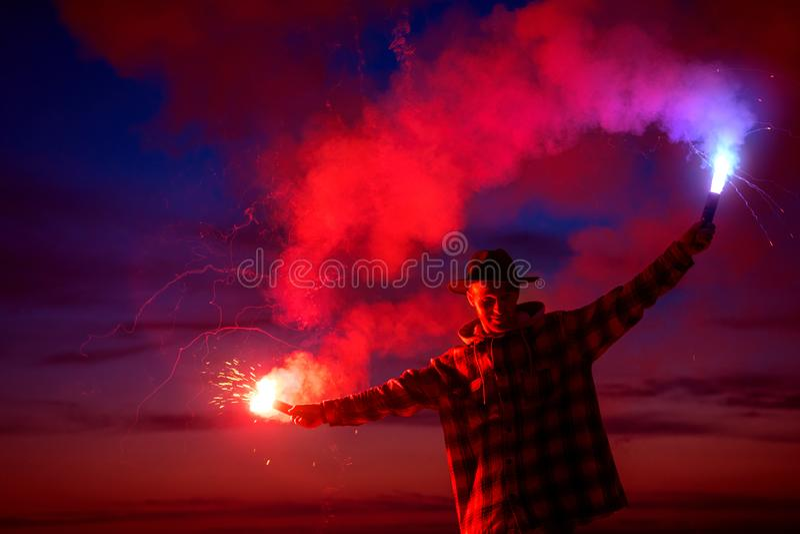 Man med signalfacklan mot mörk solnedgånghimmel royaltyfria foton