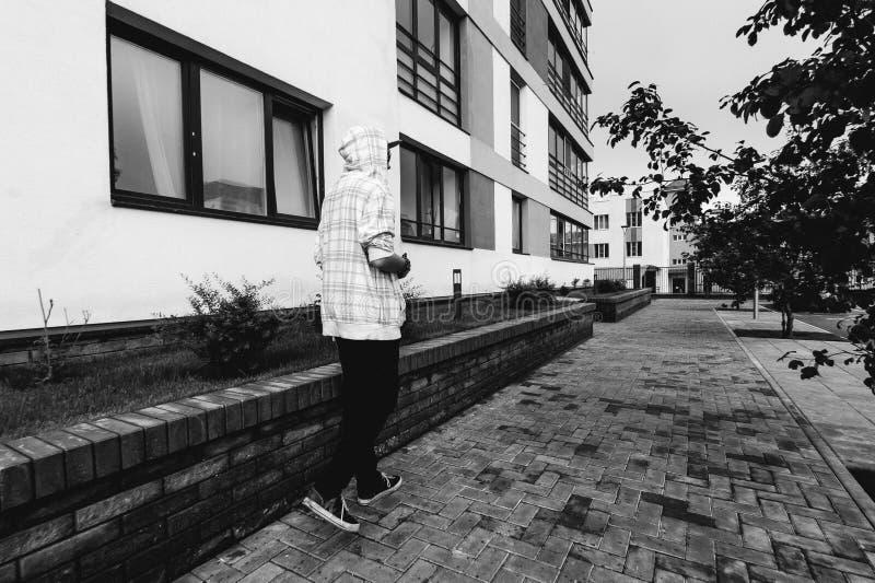 Man med skägget i ljust rutigt omslag med huven som fritt går runt om stad royaltyfri fotografi
