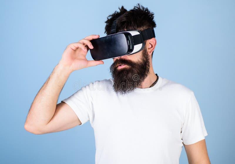Man med skägget i VR-exponeringsglas, ljus - blå bakgrund Hipster på den moderna grejen för allvarligt framsidabruk som undersöke arkivfoton