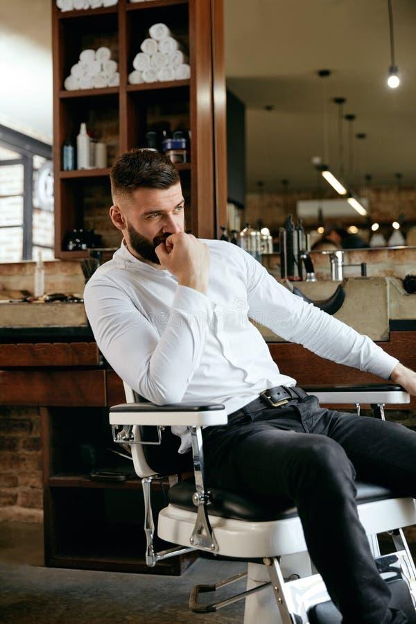 Man med skägget och frisyr i Barber Shop royaltyfri bild