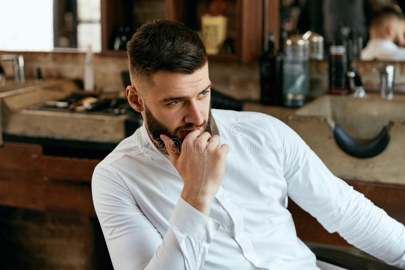 Man med skägget och frisyr i Barber Shop royaltyfria foton