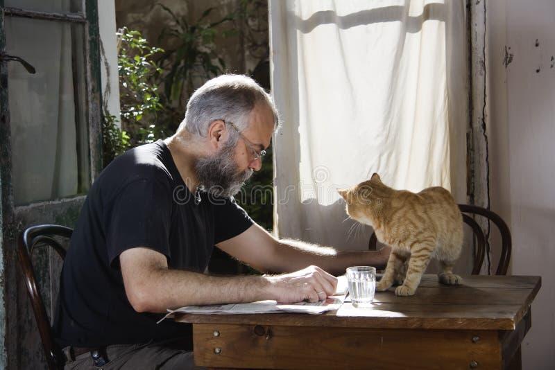 Man med skägget och hans katt royaltyfri foto