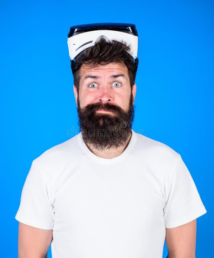 Man med skägget och mustasch med VR-exponeringsglas Bärande virtuell verklighetskyddsglasögon för man Studioskott, blå bakgrund V royaltyfri fotografi