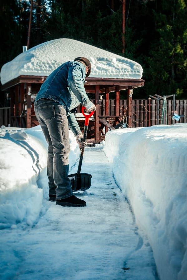 Man med skyffeln som tar bort snö från trottoaren efter snöstorm Vintertid i det fria som gör klar snö från trädgård fotografering för bildbyråer
