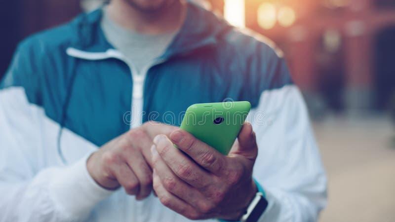 Man med smartphonemaskinskrivningtext i budbärare, solnedgång på gatan arkivfoto