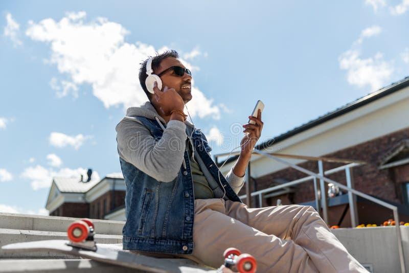 Man med smartphonen och hörlurar på taköverkant royaltyfria foton
