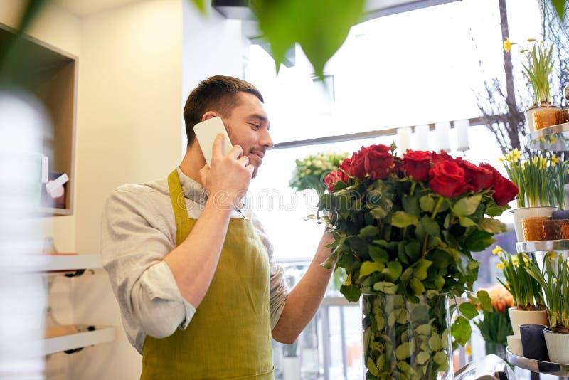 Man med smartphonen och röda rosor på blomsterhandeln royaltyfri foto