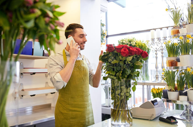 Man med smartphonen och röda rosor på blomsterhandeln fotografering för bildbyråer