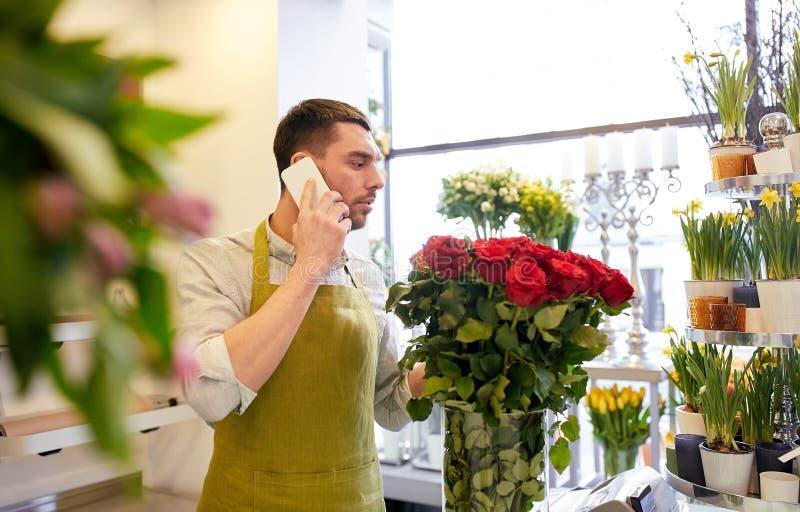 Man med smartphonen och röda rosor på blomsterhandeln arkivbilder