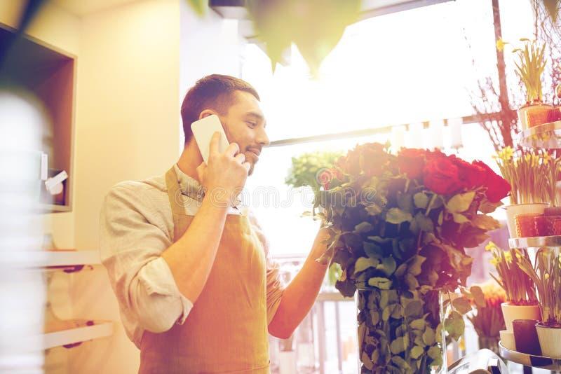 Man med smartphonen och röda rosor på blomsterhandeln arkivfoto