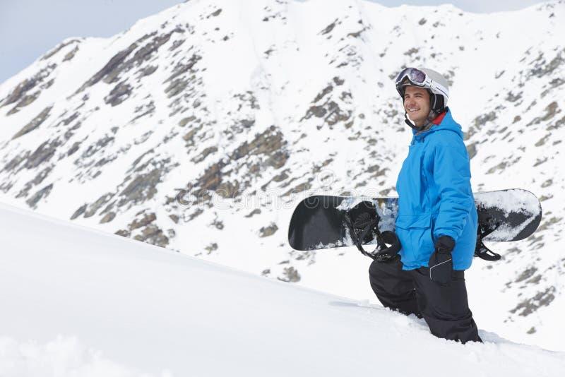 Man med snowboarden på Ski Holiday In Mountains royaltyfria foton