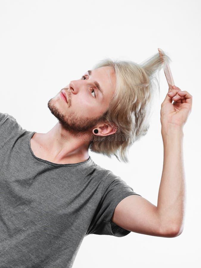 Man med stilfull frisyr som kammar hans hår arkivfoto