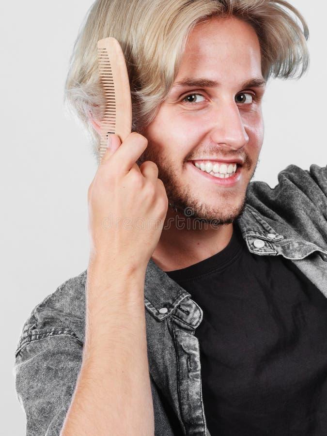 Man med stilfull frisyr som kammar hans hår arkivfoton