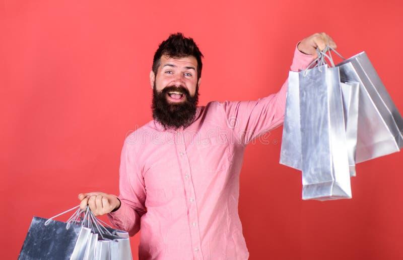 Man med stora hållande silverpappers- påsar för leende och för skägg, försäljningsbegrepp Skäggig man i rosa skjorta på röd bakgr arkivfoton
