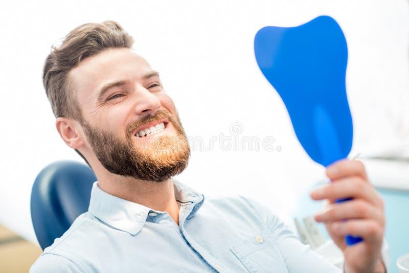 Man med stort leende på det tand- kontoret royaltyfri fotografi