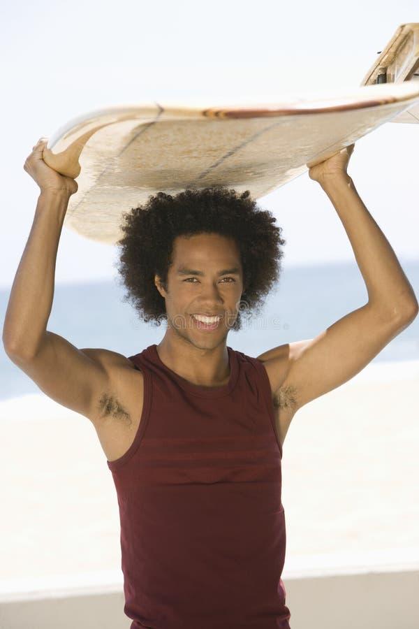 Man med surfingbrädan på huvudet på stranden arkivbild