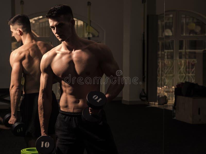 Man med torson, muskulöst macho och hans reflexion i spegelbakgrund Mannen med den näcka torson i idrottshall tycker om hans spor royaltyfria foton