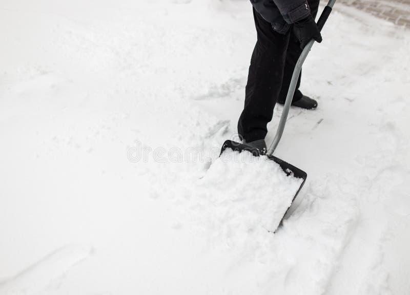 Man med trottoarer för snöskyffelrengöringar arkivfoton