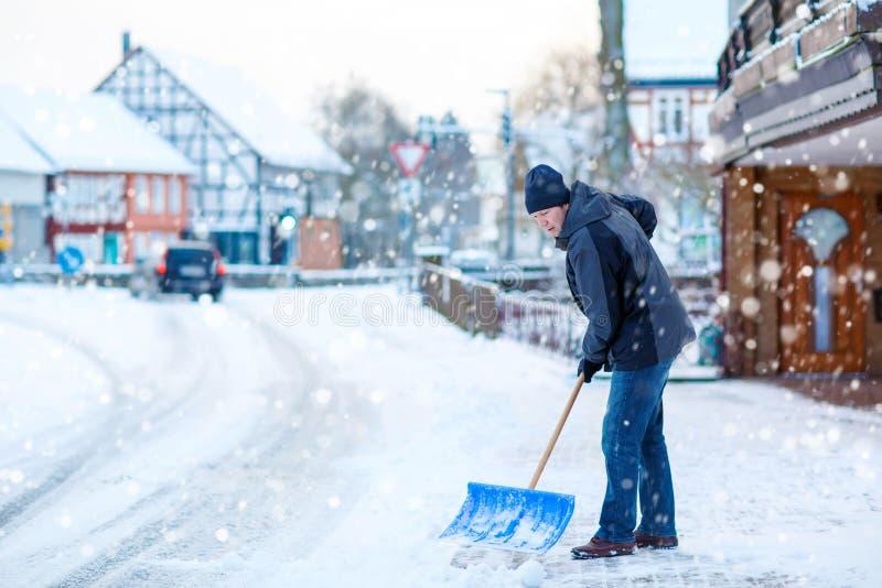 Man med trottoarer för snöskyffelrengöringar i vinter royaltyfria bilder