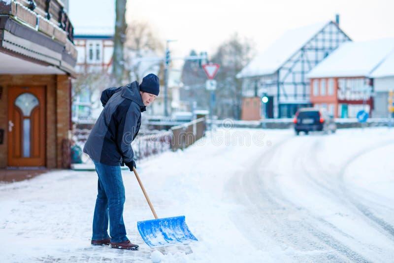 Man med trottoarer för snöskyffelrengöringar i vinter arkivbild