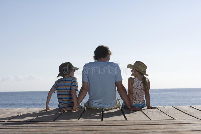 Man med två ungar som sitter på bryggan arkivfoton
