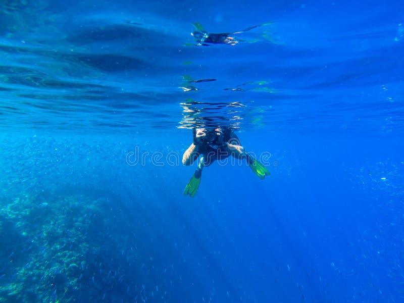 Man med undervattens- photocamera i blått havsvatten Snorkla i tropisk sj?sida Sommarsemester i den exotiska ?n arkivbilder