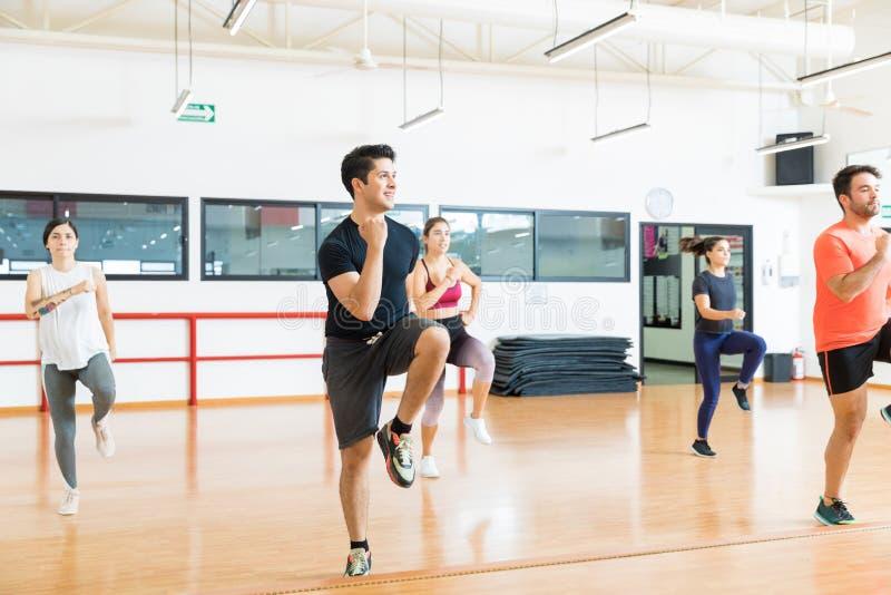 Man med vänner som utför hög knäspring i aerobicsgrupp royaltyfria bilder