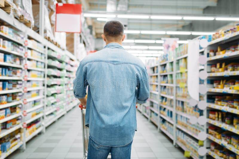 Man med vagnen i supermarket, tillbaka sikt royaltyfria foton