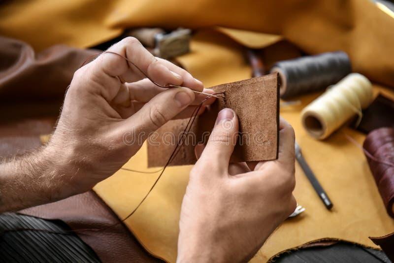 Man med visaren som syr läder i seminarium royaltyfria bilder