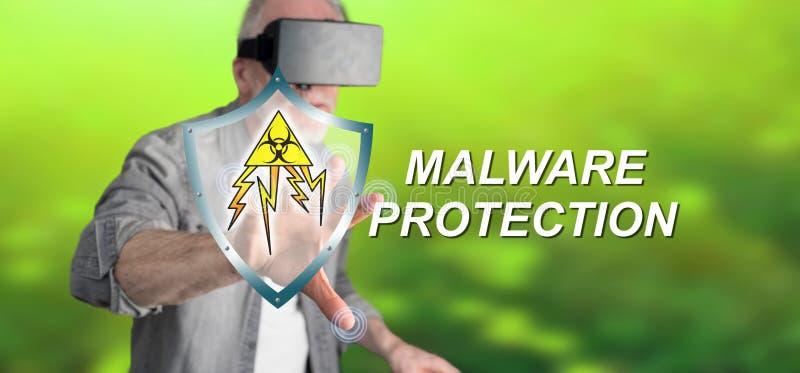 Man med VR-hörlurar med mikrofon som trycker på ett malwareskyddsbegrepp på en pekskärm royaltyfri foto