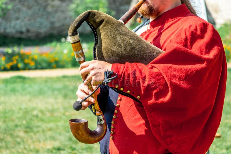 A man in a medieval red suit plays on bagpipe.  royalty free stock photos
