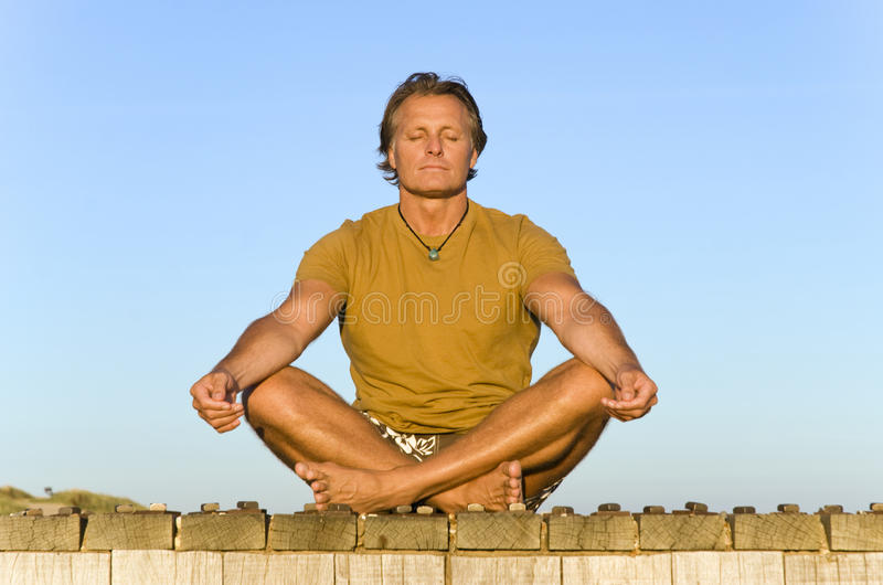 Man meditating. Colour photo of a handsome mature man sitting cross legged on the boardwalk at the beach and meditating stock image