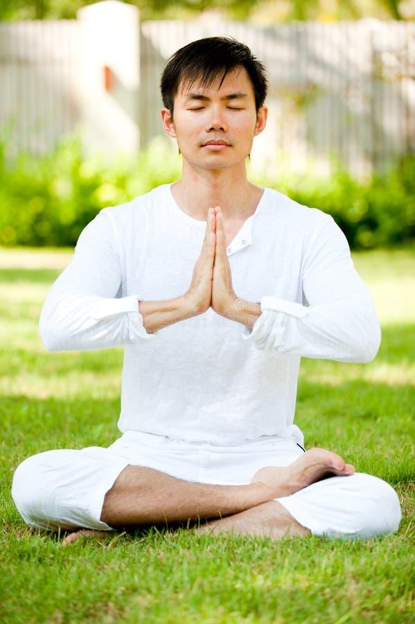 Man Meditating. An attractive asian man meditating outdoors in a garden stock photo
