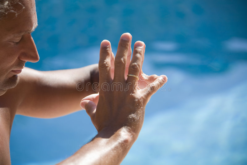 Man meditating. At the swimming pool side royalty free stock images