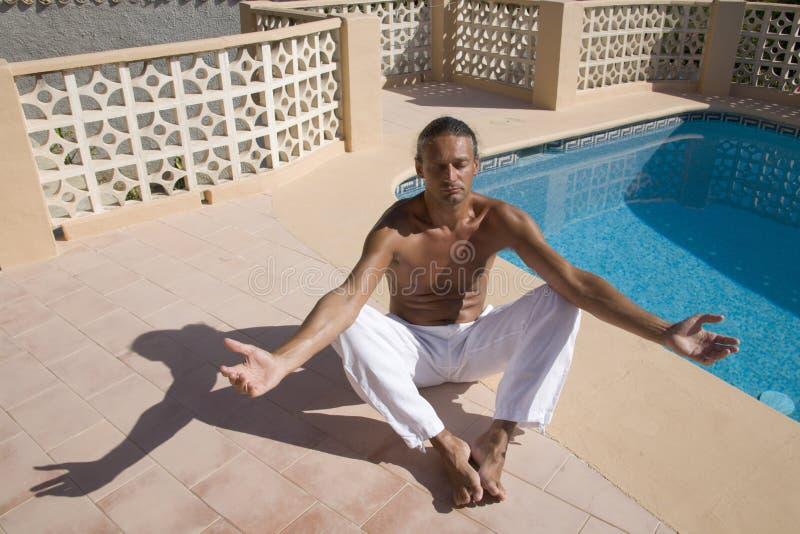 Man meditating. At the swimming pool side royalty free stock image