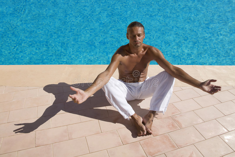 Man meditating. At the swimming pool side stock image