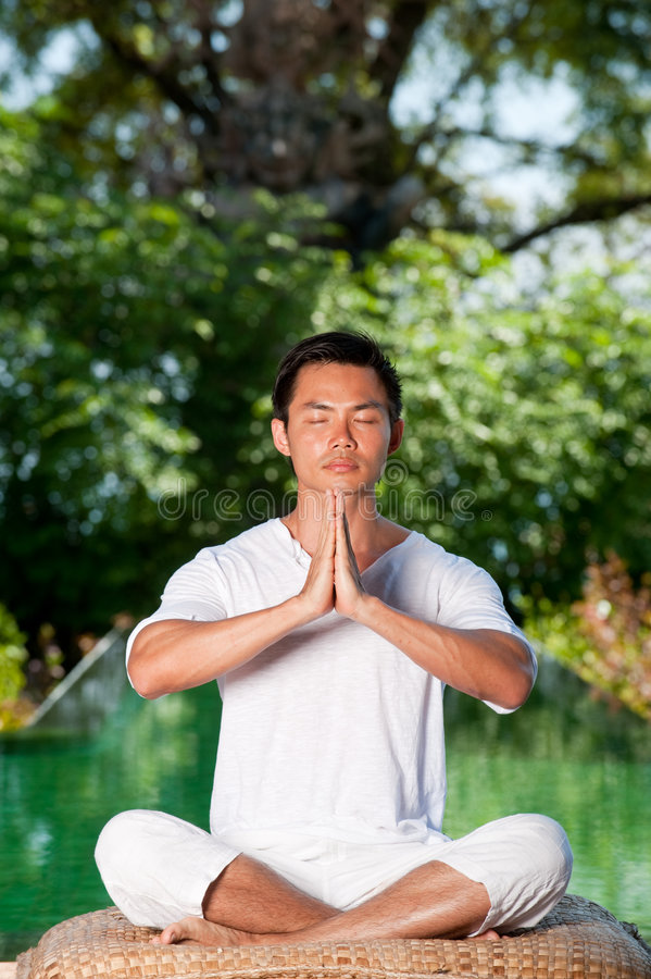 Man Meditating. A young Chinese man meditating outside with trees and pool behind royalty free stock photo