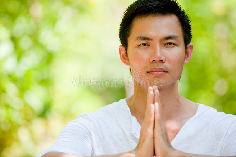Man Meditating. A young Chinese man meditating outside stock photography