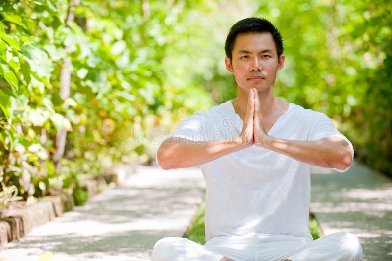 Man Meditating. A young Chinese man meditating outside stock photos