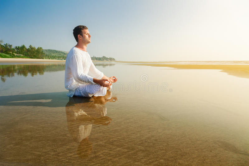 Man meditating. Man doing yoga asana meditating in a lotus position stock photography