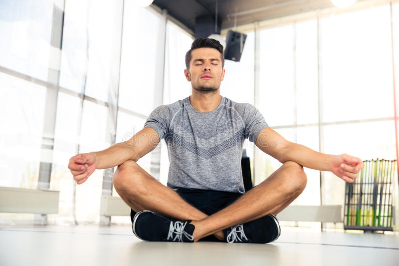Man meditating in fitness gym. Portrait of a handsome man meditating in fitness gym royalty free stock photo