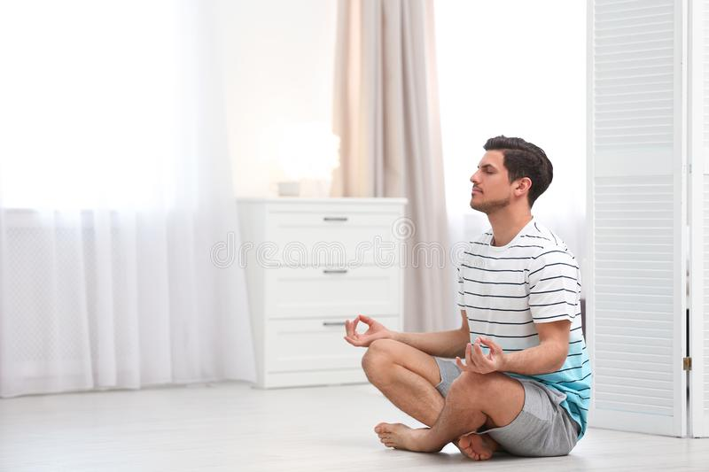 Man meditating on floor at home, space for text. royalty free stock photos