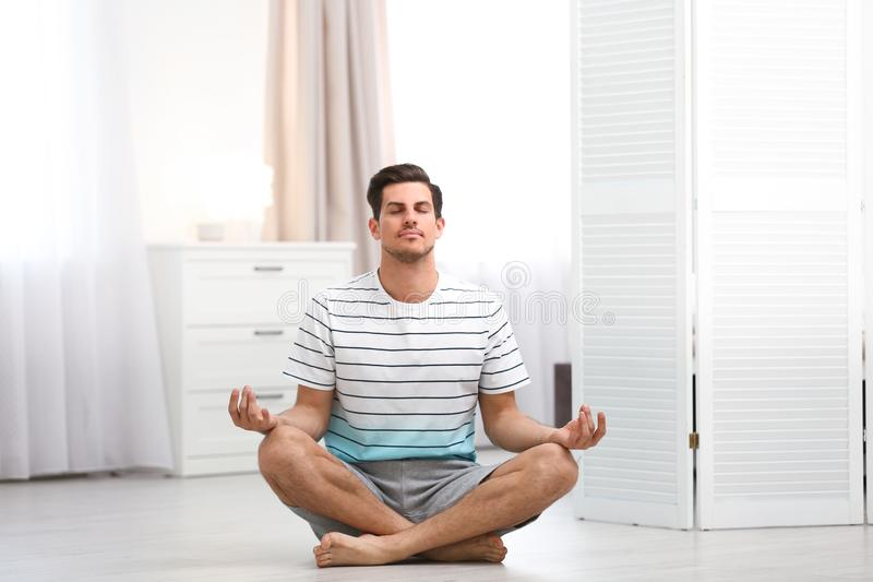 Man meditating on floor at home royalty free stock image