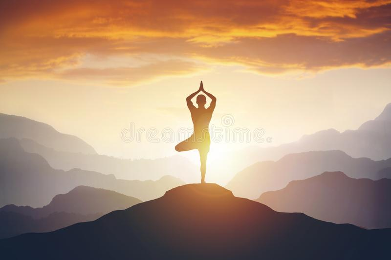 Man meditating on high mountain in sunset background royalty free stock photography